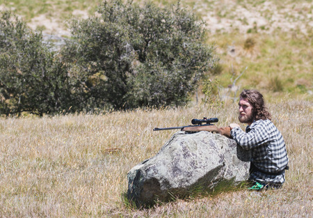 gun: Hunter with a rifle sits near boulder