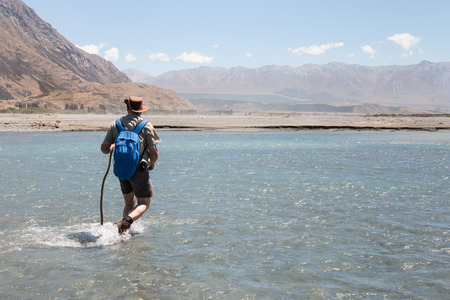 guy with walking stick: Elderly man with a backpack crossing a river ford, Rangitata River, New Zealand