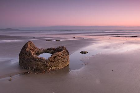 fraction: Fraction of a boulder on the ocean shore at sunrise, Moeraki boulders, New Zealand