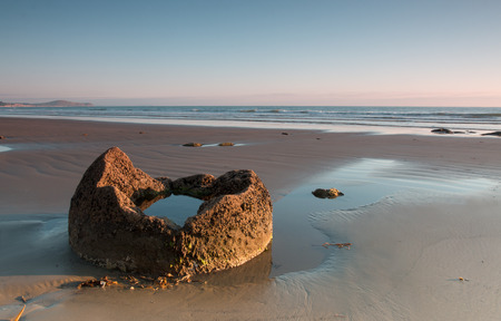 spall: Fragment of a boulder on the ocean shore at sunrise, Moeraki boulders, New Zealand