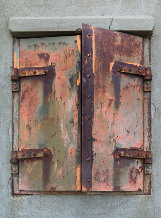 eliminated: Window of an abandoned building with rusty iron shutters Stock Photo