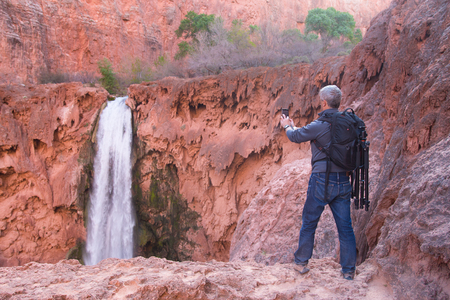 packsack: Man with photo gear takes picture of Mooney Falls with his mobile phone, Havase Canyon, Arizona, USA Stock Photo
