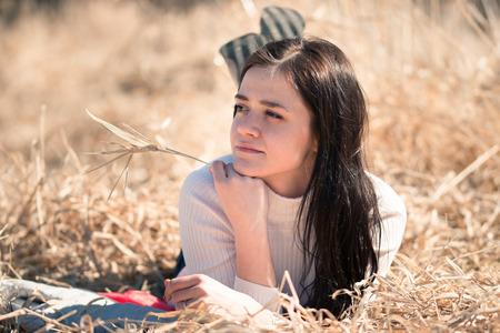 lies down: Young beautiful girl lies down on dry yellow grass Stock Photo