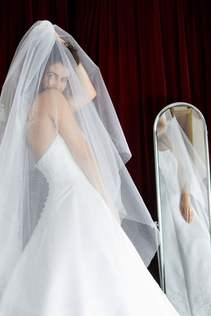 Bride with dark complexion and curly black hair, wearing a wedding dress and looks at herself in the mirror photo