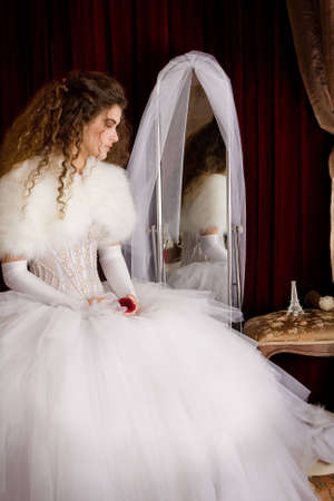 The bride with long brown curly hair in a wedding dress sitting at the mirror and holds in her hands a rose photo