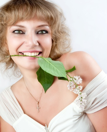 eastern european ethnicity: A young woman holds the teeth sprig of lilac. She smiles and looks straight at the camera. White background