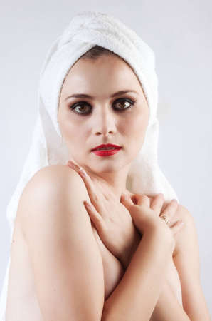 Young beautiful girl in the sauna towel looks directly at the camera. The background is white. photo