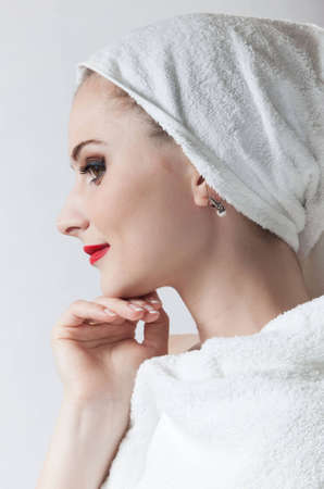 Young beautiful girl in the sauna towel stands in profile to the camera. The background is white. photo