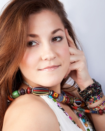 eastern european ethnicity: Portrait of a Young Woman with beads on her neck and bracelets on her arm. She looks into the camera. The background is white.