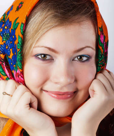 eastern european ethnicity: young girl is dressed in a bright head scarf. She props up the hands of a cheek and smiles in a camera Stock Photo
