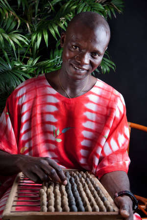 The African man holds a wooden abacus in the hands  He looks in the camera  A background black  photo