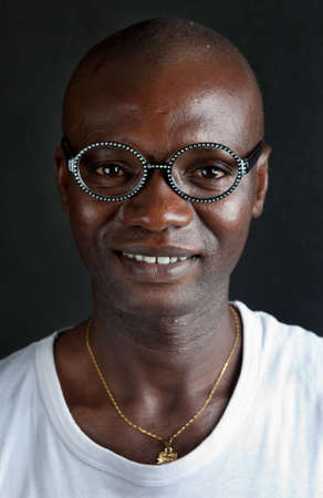 The young African in fashion glasses looks in a camera and smiles  A background black photo