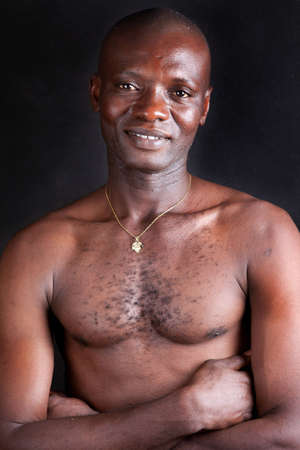 Portrait of the African young manThe young African has well developed muscles  He looks at the camera   A background black  photo