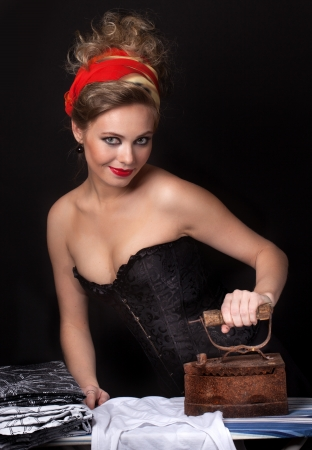 woman ironing:  young girl in a corset irons clothes Stock Photo