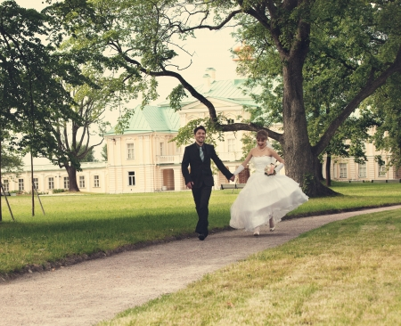 eastern european ethnicity:  groom and the bride run on a path in palace park