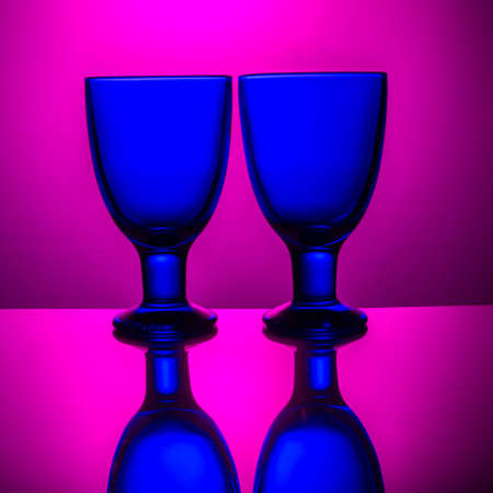 luminosity: Two brightly blue glasses are lit brightly pink light Stock Photo