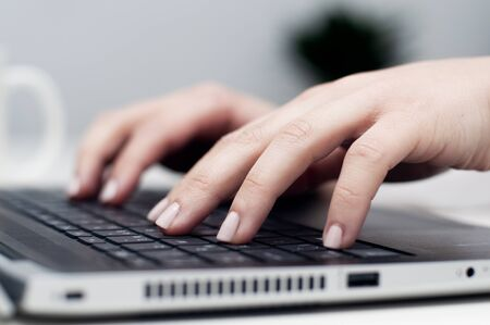 Closeup female hands typing on laptop keyboard. Young caucasian woman working on laptop, pressing keys. Work from home, stay at home, home office, remote work or telecommuting concept. Imagens