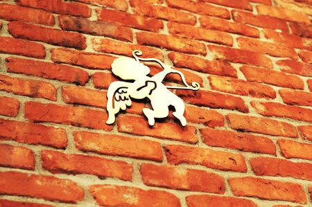 An angel or cupid with a bow and arrow on brick wall background. Concept of love or wedding.