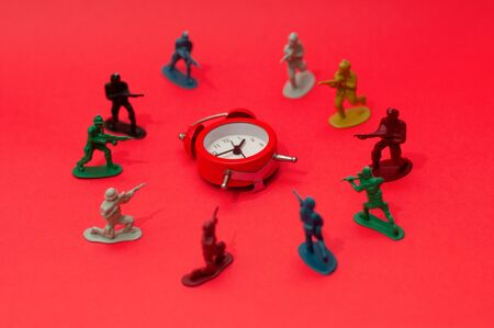 Toy soldiers surrounding a fallen alarm clock. Killing time, wasting time, stop time, time management, deadline, overtime concept.