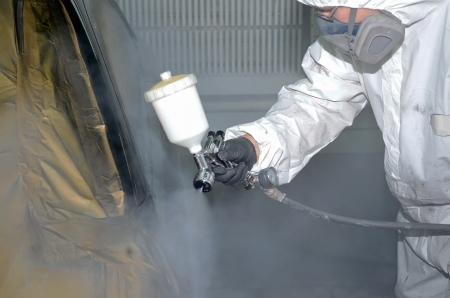 Professional auto painter paints the car after the car body repairs