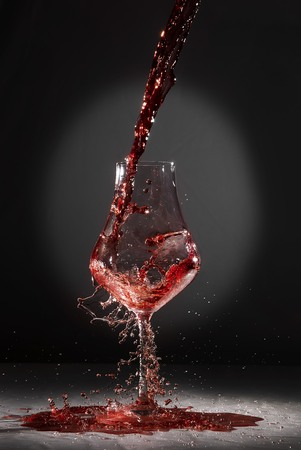 poured: Wine incautiously poured into crystal goblet. Stock Photo