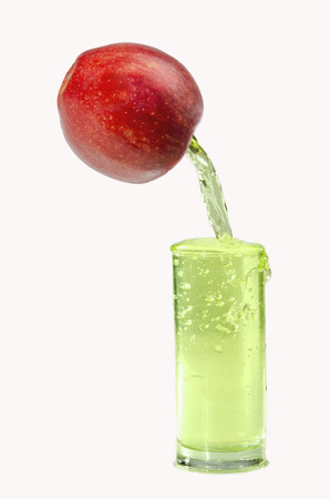 allocated on white: Apple juice is poured into a glass of ripe red apple. Is allocated on a white background.