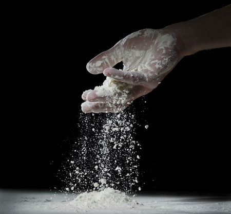 baking ingredients: Wheat flour is poured from a mans palm. Stock Photo