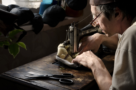Master making leather goods behind work.