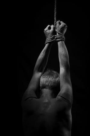 Hombre suspendido de una cuerda en la mano.
