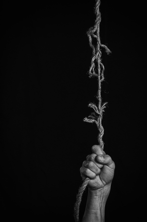 Man clings to a rope that breaks off. 写真素材