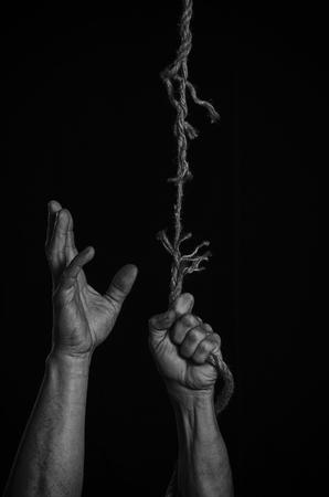 Man clings to a rope that breaks off. 版權商用圖片