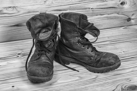 Old military boots on a wooden table in black and white.