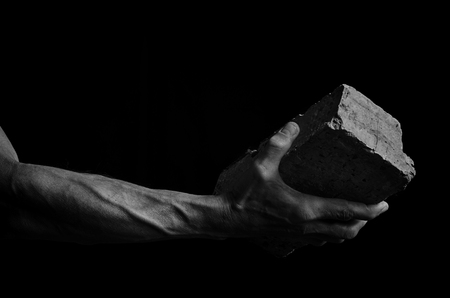 Man's hand holding a brick, in black and white.