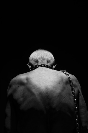 Slavery. A man tied with a chain over his neck in black and white.