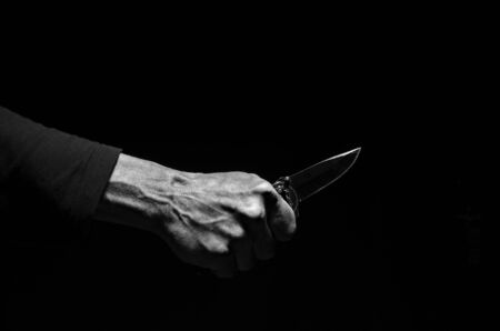 Male hand with a knife in black and white.