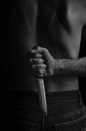 Ein Mann versteckt ein Messer in Schwarz-Weiß hinter seinem Rücken.