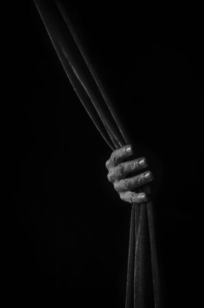 A male hand holds a curtain in black and white.