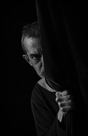 A frightened man peeks out from behind a curtain in black and white.