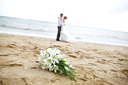 해변에서 부부와 함께 결혼식 꽃다발
