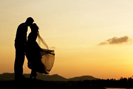 siluetas de mujeres: par de la boda con la puesta de sol