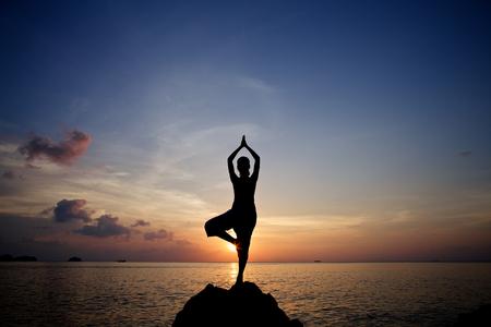 요가 포즈 열 대 해변에서 연습하는 젊은 여자 명상 실루엣