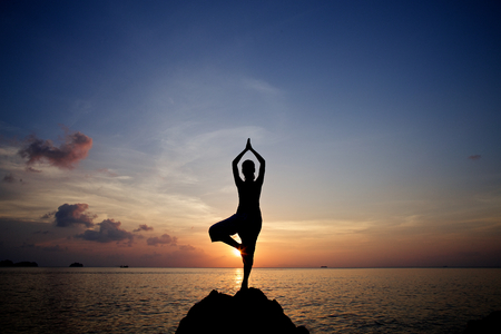 silhouette young woman meditation practicing yoga pose on the tropical beach