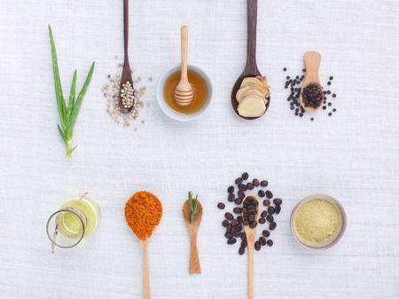herb variety on rustic white background from top view, oil, coffee, beans, pepper, aloe vera, turmeric, ginger, rosemary