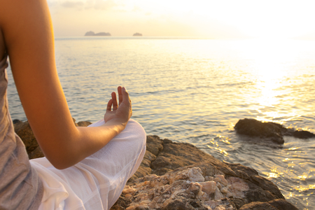 young woman meditation in a yoga pose on the tropical beach photo
