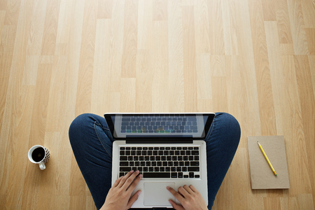 girl sitting on a wooden floor laptop coffee cup and notebook Standard-Bild