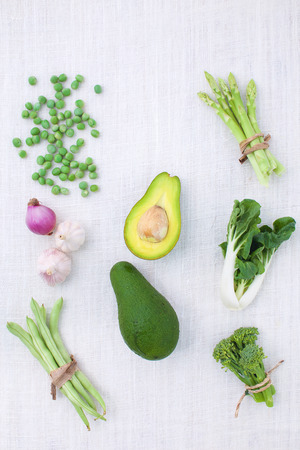 Fresh green vegetables variety on rustic white background from top view, broccoli, celery, avocado, pepper, peas, beans, lettuce,