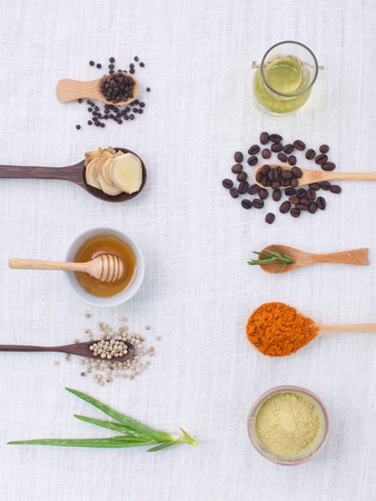 spa treatments: herb variety on rustic white background from top view, oil, coffee, beans, pepper, aloe vera, turmeric, ginger,