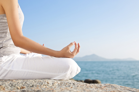 persona respirando: joven meditación mujer en una pose de yoga en la playa tropical
