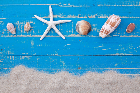 white sand star fish and shells on blue wooden background