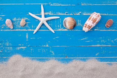 wit zand zeesterren en schelpen op blauwe houten achtergrond